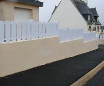 Scellement d'une clôture pvc blanche sur muret parpaings